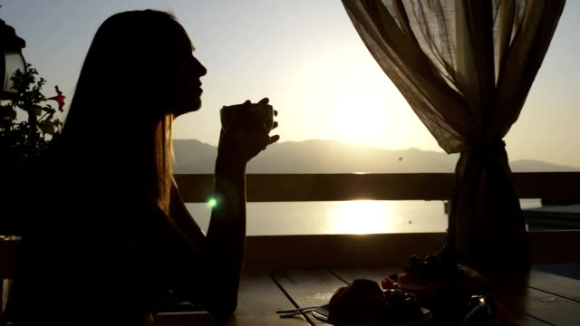 silhouette of young woman sits in a cafe with panoramic views of sea bay. - portico video stock e b–roll