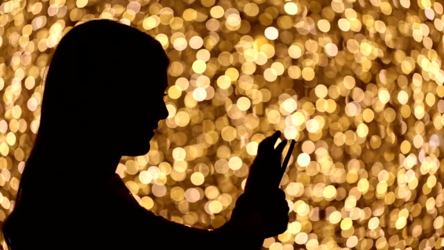 silhouette of young woman using smart phone video