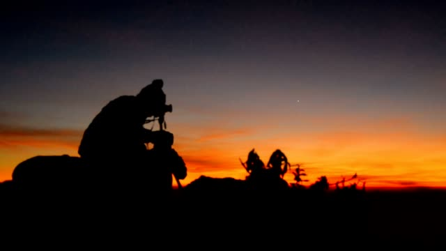 Silhouette : panning photographers on peak of mountain video