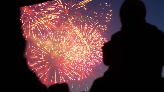 Silhouette people enjoying holiday firework closeup on weekend in night sky 4K