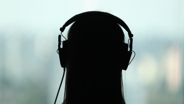 Silhouette person putting headphones ON. Back woman listening to song, audiobook, or podcast