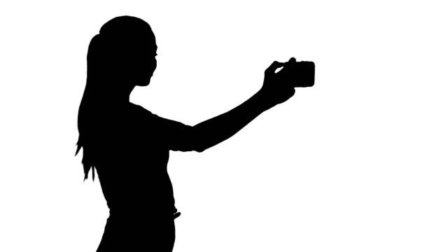 Niña bonita silueta tomando un selfie y caminar - vídeo