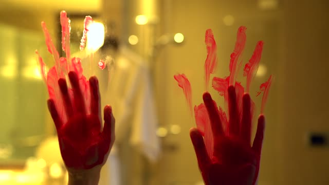 Silhouette scared girl hand with red blood behind a glass door, horror background.
