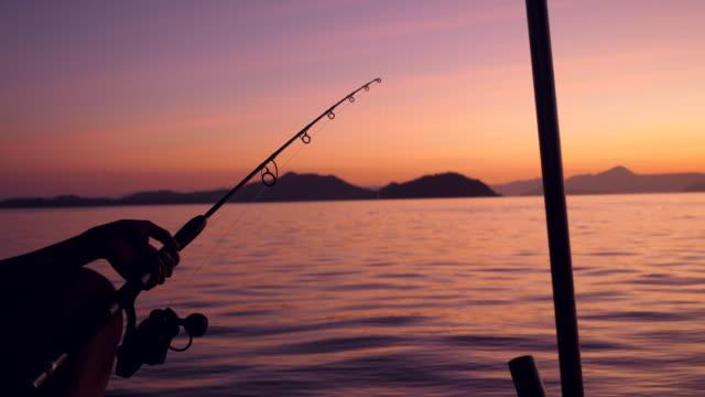 silhouette scene of fisherman hold fiskespön bredvid lugna havet vid soluppgången - fiskebåt bildbanksvideor och videomaterial från bakom kulisserna