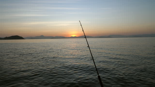 Silhouette Scene of Fishing Rods with Tranquil Ocean at Sunrise