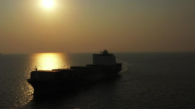 vídeos de stock, filmes e b-roll de vista aérea do navio silhueta sobre o oceano - navio tanque embarcação industrial