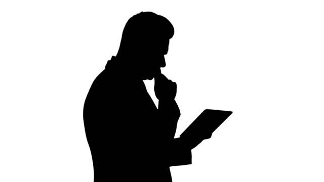 Silhouette Smart senior businessman using a technology tablet
