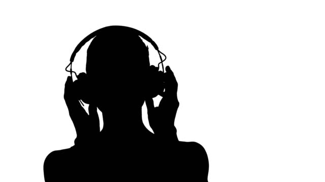Silhouette Smiling young woman listening to music with headphones