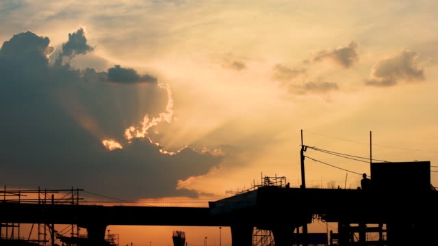 Silhouette Sunlight shining through the clouds over construction site Time lapse