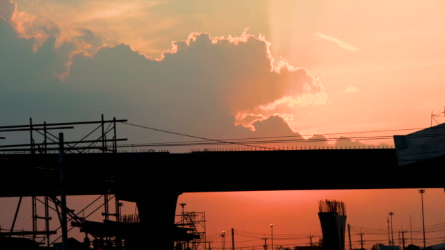 Silhouette Sunset and clouds over construction site Time lapse