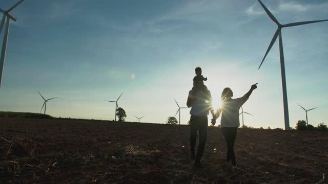 家族のシルエットの夕日、男の子は父の首に乗って、大きな自由を持って風力タービンの間を歩きながら彼の妻を握ります。ヘルプハンズのコンセプト。 - 希望点の映像素材/bロール