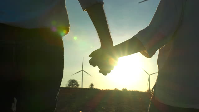 vídeos de stock e filmes b-roll de silhouette sunset of two people holding hand while walk between the wind turbines with great freedom.helping hands concept. - economia circular