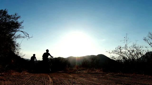sagoma due persone mountain bike, equitazione al tramonto - percorso per bicicletta video stock e b–roll