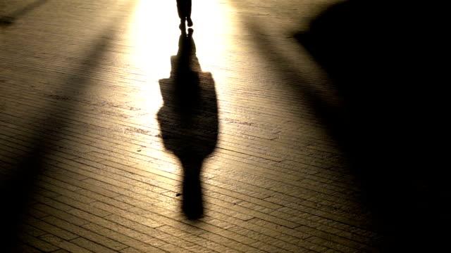 vidéos et rushes de silhouette personne méconnaissable marchant au ralenti - ombre