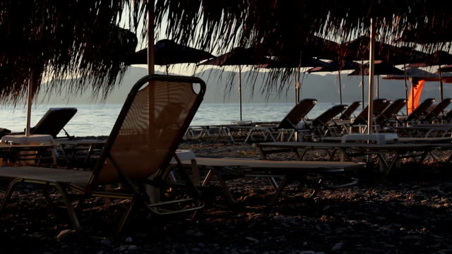 Silhouette view of thatched umbrellas with loungers next to the coastline video