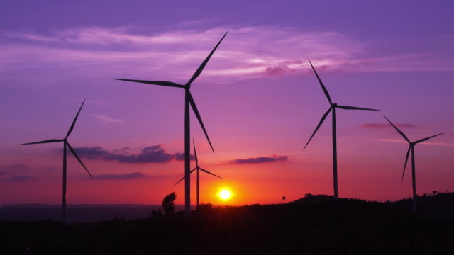 silhouette wind turbines farm at sunset - turbina a vento video stock e b–roll