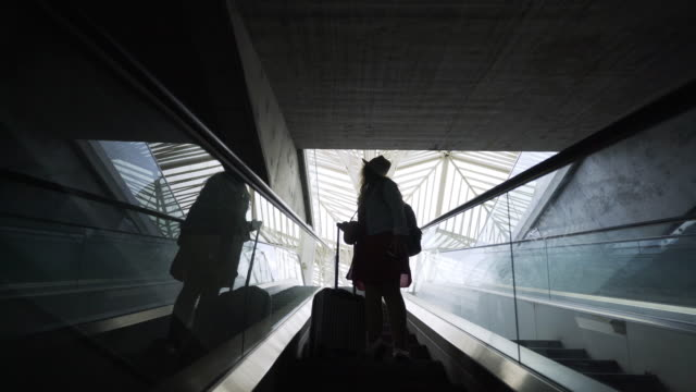 silhouette woman passenger on moving stairs - escalator video stock e b–roll