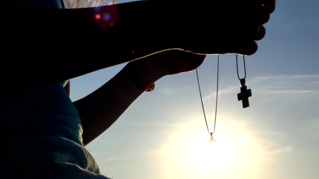 Silhouette woman praying with cross on beautiful sunset video