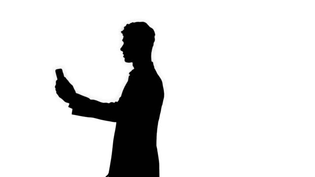 Silhouette Young business man walking and taking a selfie