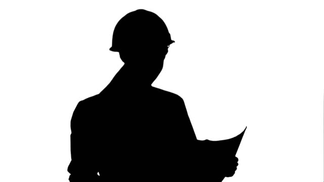 Silhouette Young female architect holding blueprints and checking construction video