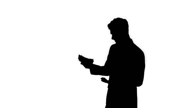 silhouette ung lycklig affärsman dansar efter att ha räknat lön. vinn dans - spendera pengar bildbanksvideor och videomaterial från bakom kulisserna