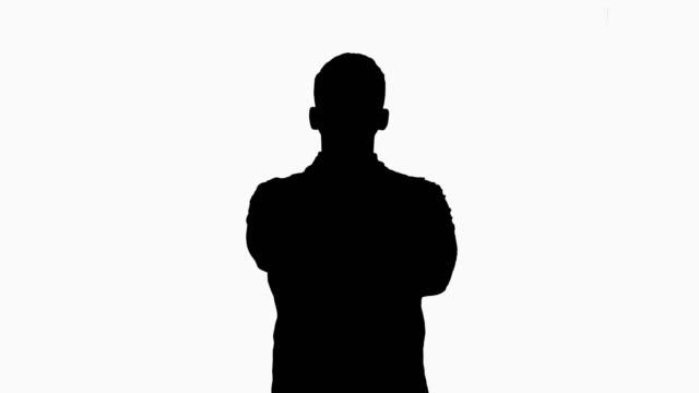 vidéos et rushes de silhouette jeune docteur caucasien mâle restant avec les mains pliées - armement