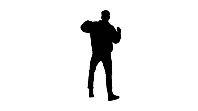 silhouette young man dancing hip-hop doing waves - hip hop video stock e b–roll