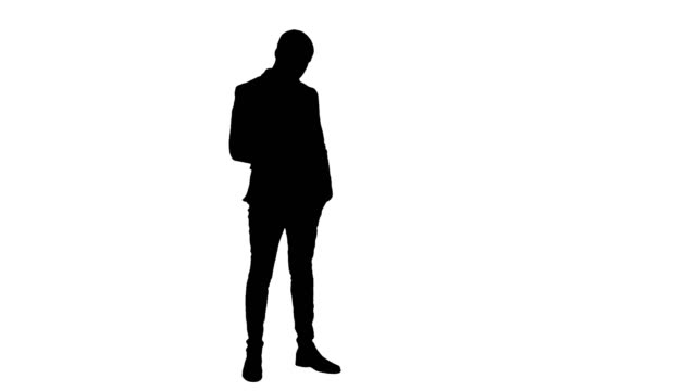 Silhouette Young man in suit sending text messages on his phone Silhouette Young man in suit sending text messages on his phone. Professional shot in 4K resolution. 065s. You can use it e.g. in your commercial video, business, presentation, broadcast video. full length stock videos & royalty-free footage