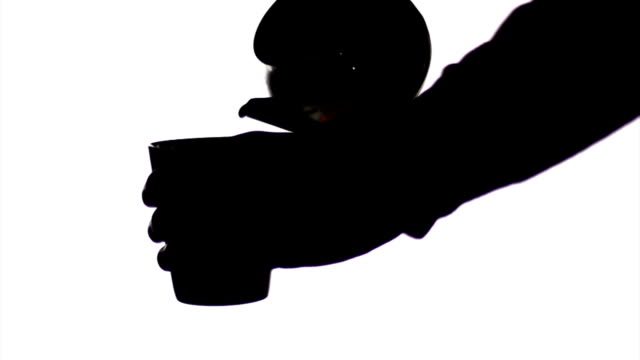 silhouette young man is serving drink with kettle and cup. - porcelain stock videos & royalty-free footage