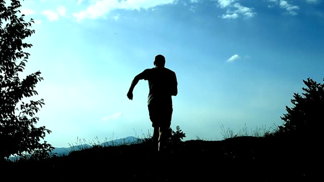 silhouette ung man går till toppen av berget och lyfter händerna som ett tecken på prestation, framgång och glädje. koncept och symbol för framgång lycka slå prestationen advance välstånd. - välstånd bildbanksvideor och videomaterial från bakom kulisserna
