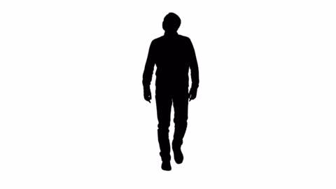 vídeos y material grabado en eventos de stock de hombre joven silueta caminar mirando fascinado - recortable