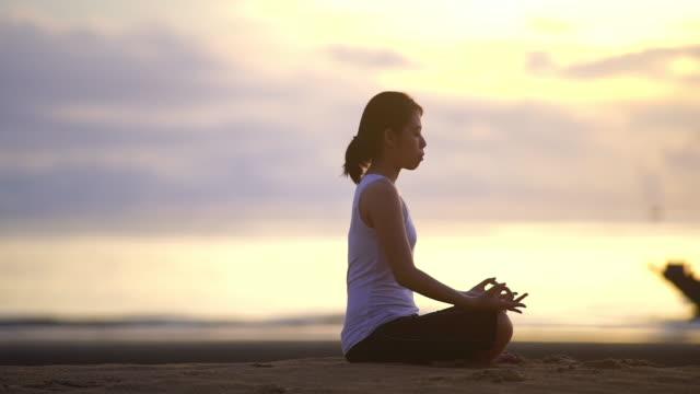 ヨガシルエットで若い女性のビーチの日の出。 - ヨガ点の映像素材/bロール