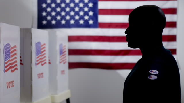 Silhouetted African American man has voting stickers taken away 4K video