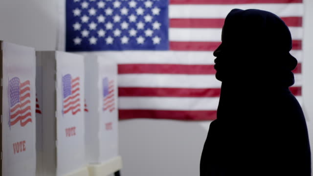 Silhouetted African American man in hoodie looking at voting booths 4K video