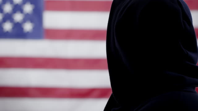 Silhouetted African American man in hoodie looks at US flag 4K video