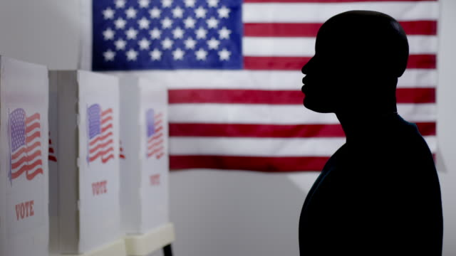 Silhouetted African American man looking at voting booths 4K video