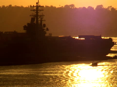 Silhouetted Boat Passes Navy Aircraft Carrier Deck at Sunset video