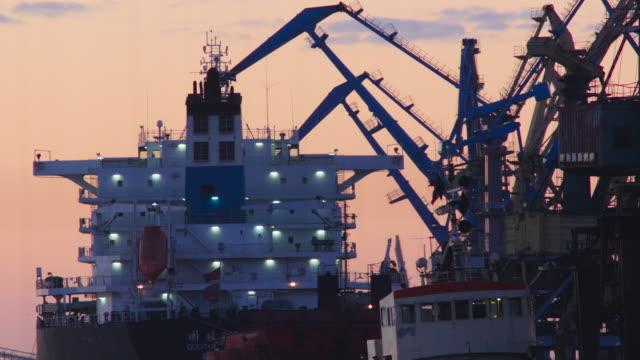 vídeos de stock, filmes e b-roll de silhueta de grous porto de carga de carga em um navio - países bálticos