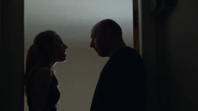 Silhouetted man and woman arguing in hallway