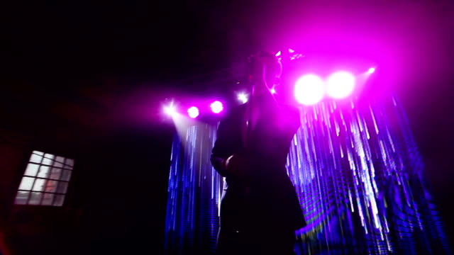 Silhouetted man sings on night club concert stage at LED screen background showing abstract animation of slowly moving waterfall lines POV. Stylish singer performs song with microphone at New Years video