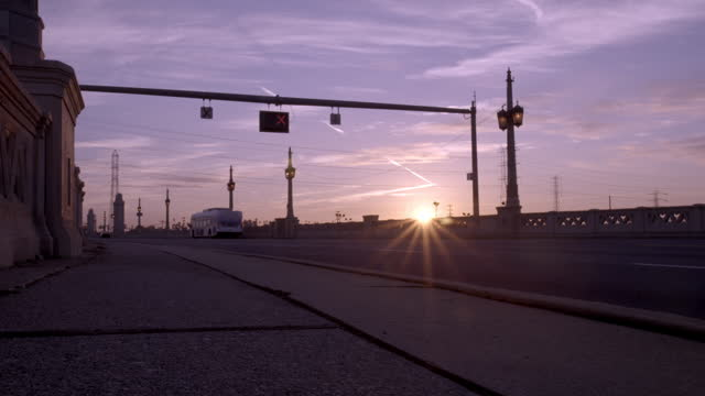 Silhouetted man walks past as cars driver over bridge at sunrise HD video