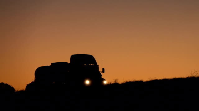 SLOW MOTION: Silhouetted oil tank truck driving along the highway in the dark