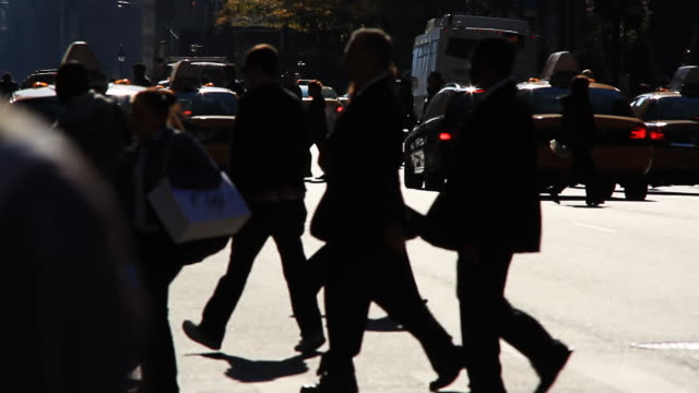 Silhouetted pedestrians and crowded city street video