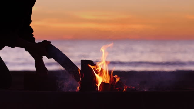 Silhouetted Person Placing Logs on Beach Bonfire - video