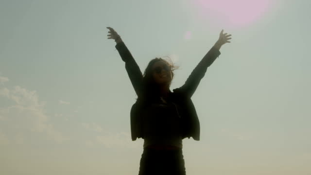 A silhouetted young woman raises her hands to the sky. video