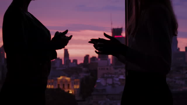 Silhouettes against skyscraper windows with sunset. Businesswomen chatting