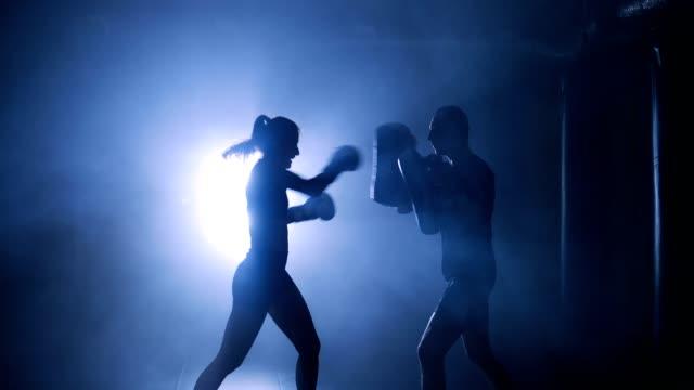 vídeos de stock, filmes e b-roll de silhuetas de um lutador de boxe feminino socando um saco de boxe com luvas de boxe em um ginásio fumarento - artes marciais