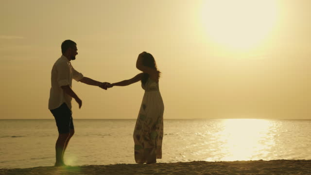 Silhouettes of a young couple, funny dancing against the backdrop of the sea and the setting sun. Merry holiday by the sea Silhouettes of a young couple, cool dancing against the backdrop of the sea and the setting sun. Merry holiday by the sea young couple stock videos & royalty-free footage