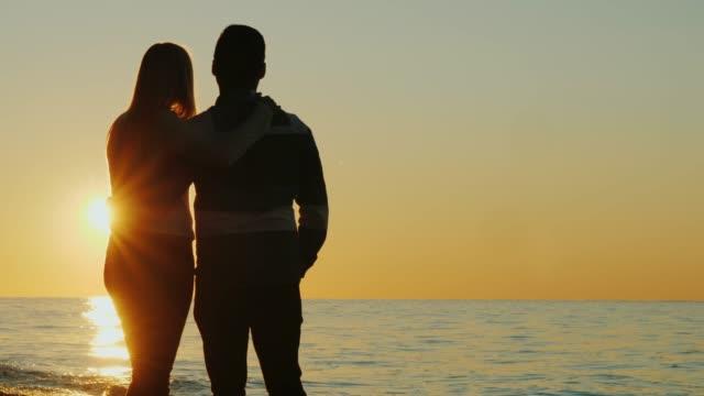 ハグと海で一緒に夕日を眺め、若いカップルのシルエット。背面図 - シルエット点の映像素材/bロール