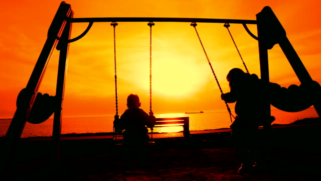 Silhouettes of children on a swing at sunset video